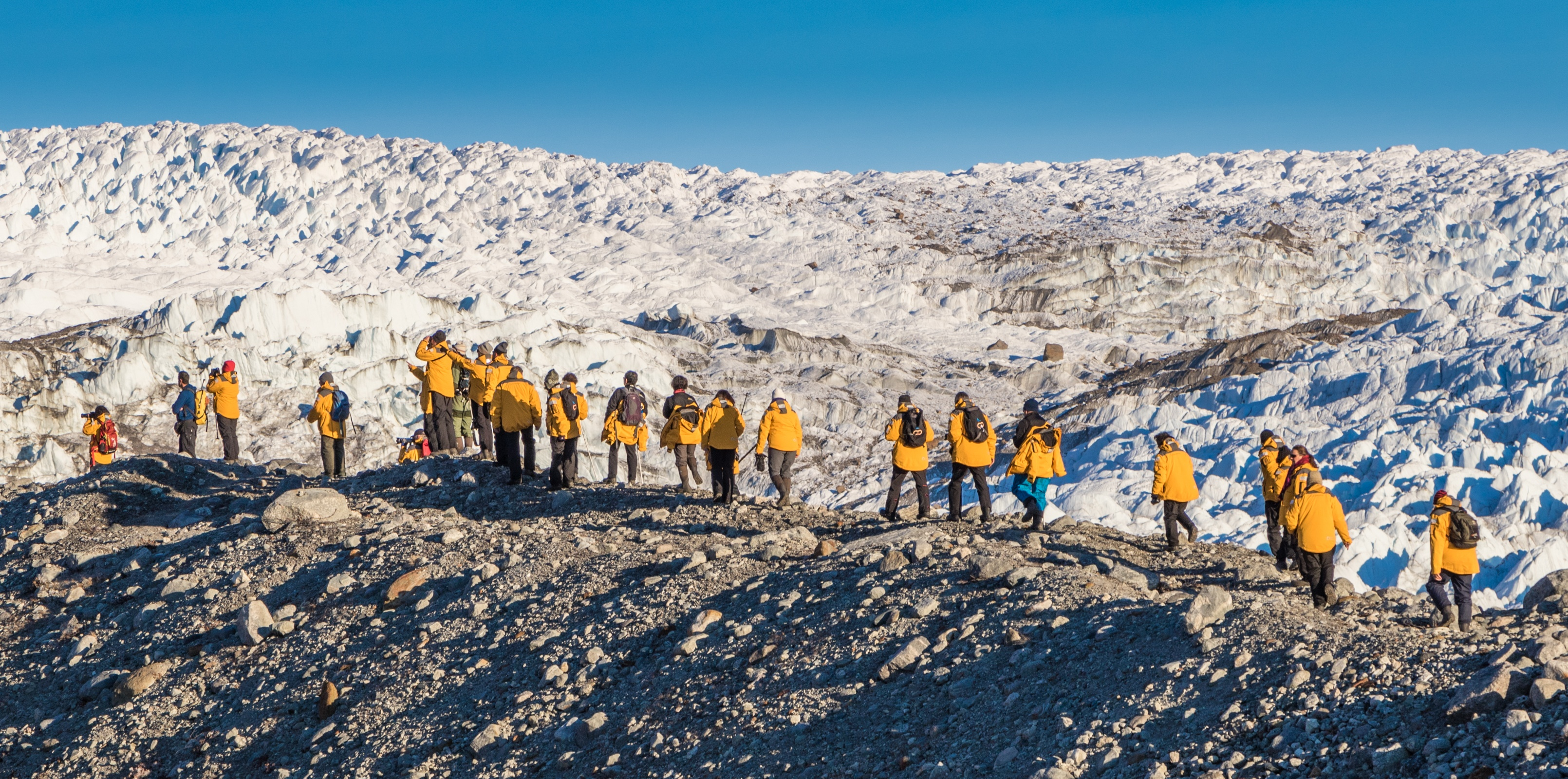 Quark passengers take a guided hike over rugged Greenland terrain on an expedition shore landing.