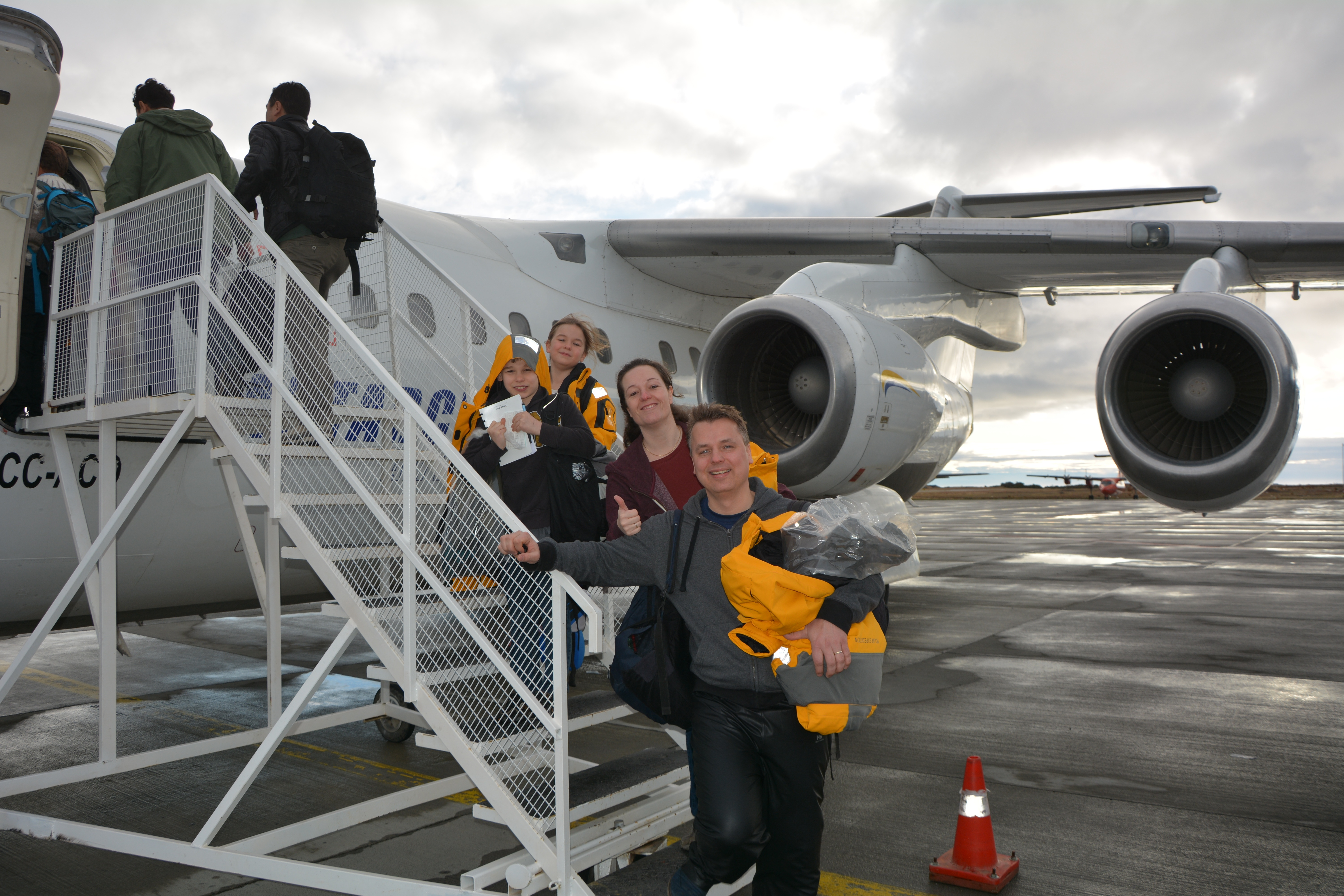 A family steps off their charter flight on a polar Fly-Cruise expedition.