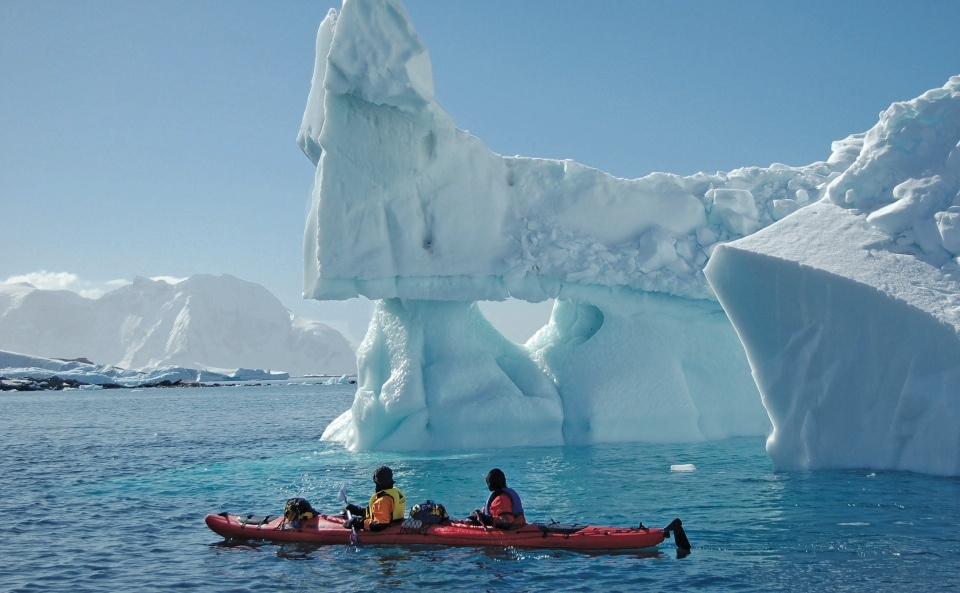 Kayakers get a close look at an iceberg in Greenland.