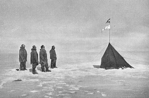 "Roald Amundsen, Helmer Hanssen, Sverre Hassel and Oscar Wisting (l–r) at ""Polheim"", the tent was upright at the South Pole on 16 December 1911. The top flag is the Flag of Norway; the bottom is marked ""Fram"". Photograph by Olav Bjaaland."