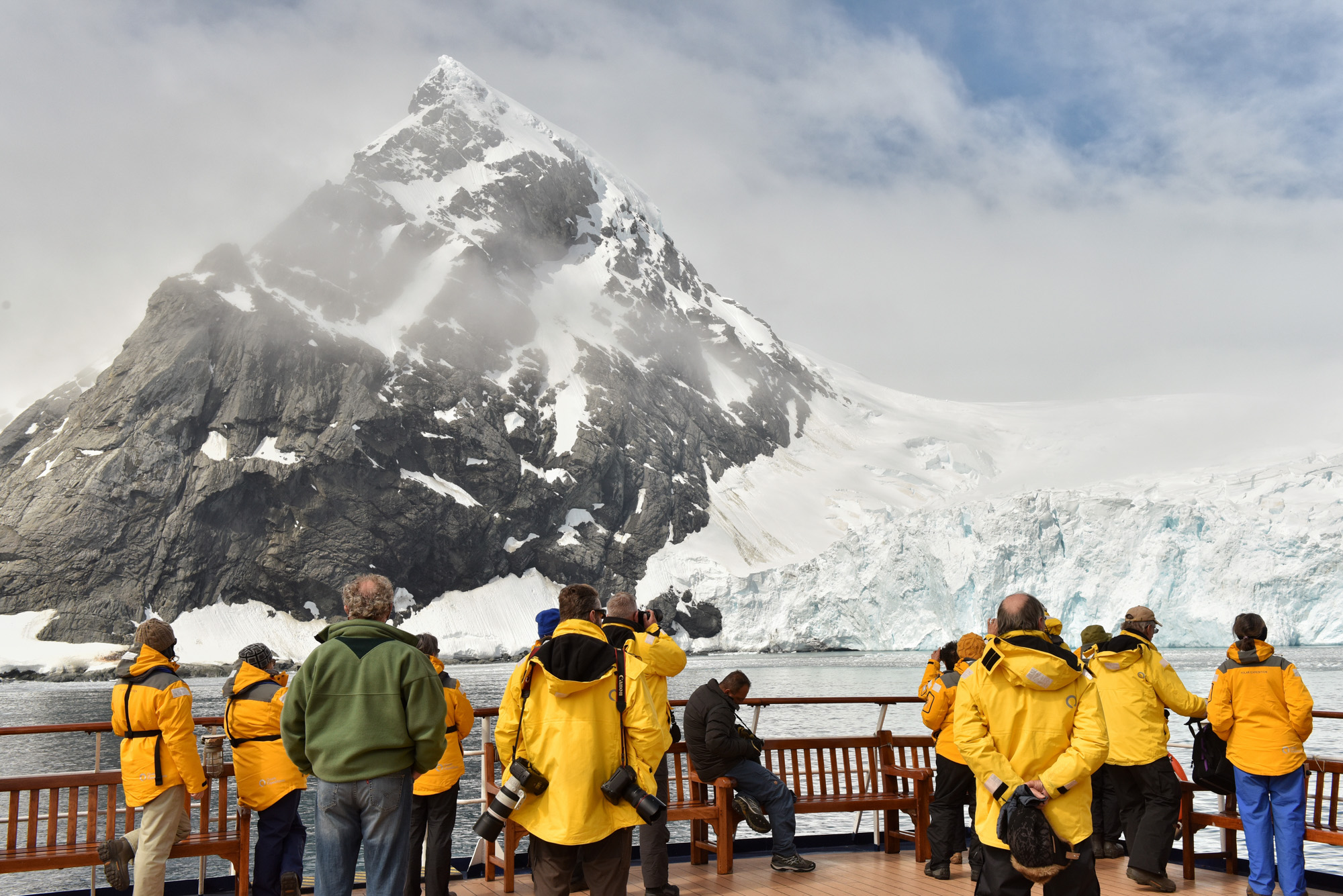 Passengers marvel at the sheer scale of Point Wild, an important Antarctic historic site.