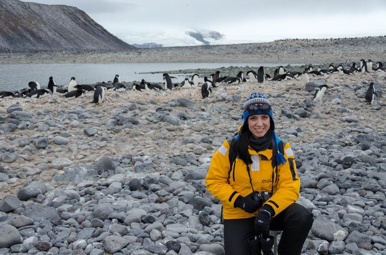 Nadine Ponte sits surrounded by penguins in Antarctica