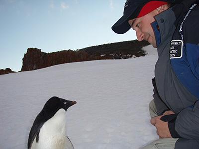 Mikolaj Golachowski and an Adelie penguin, Antarctica
