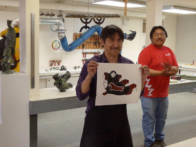 An Indigenous artisan displays his work in Cape Dorset.