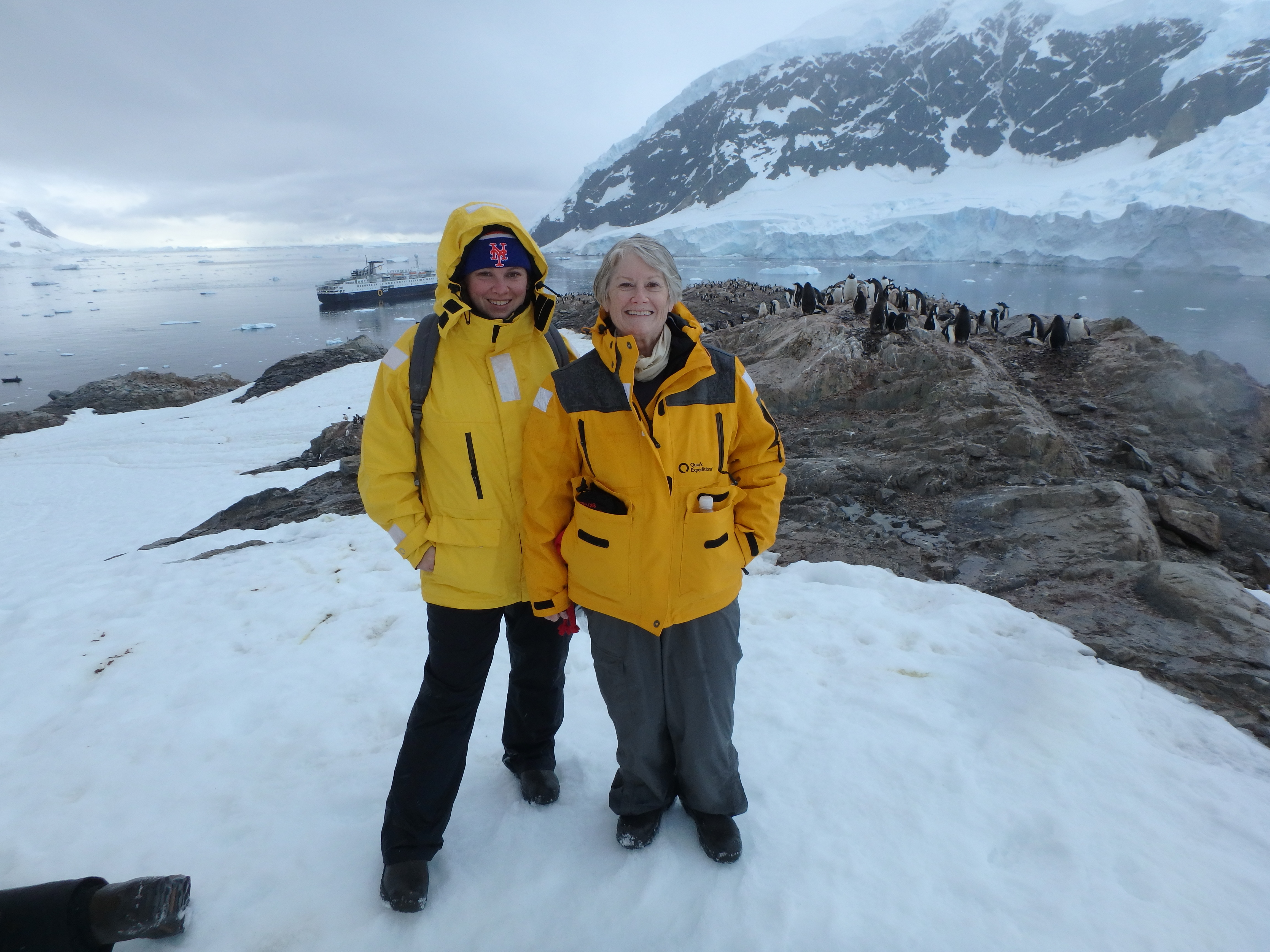 Katrina and her aunt pose with Adelie penguins in Antarctica