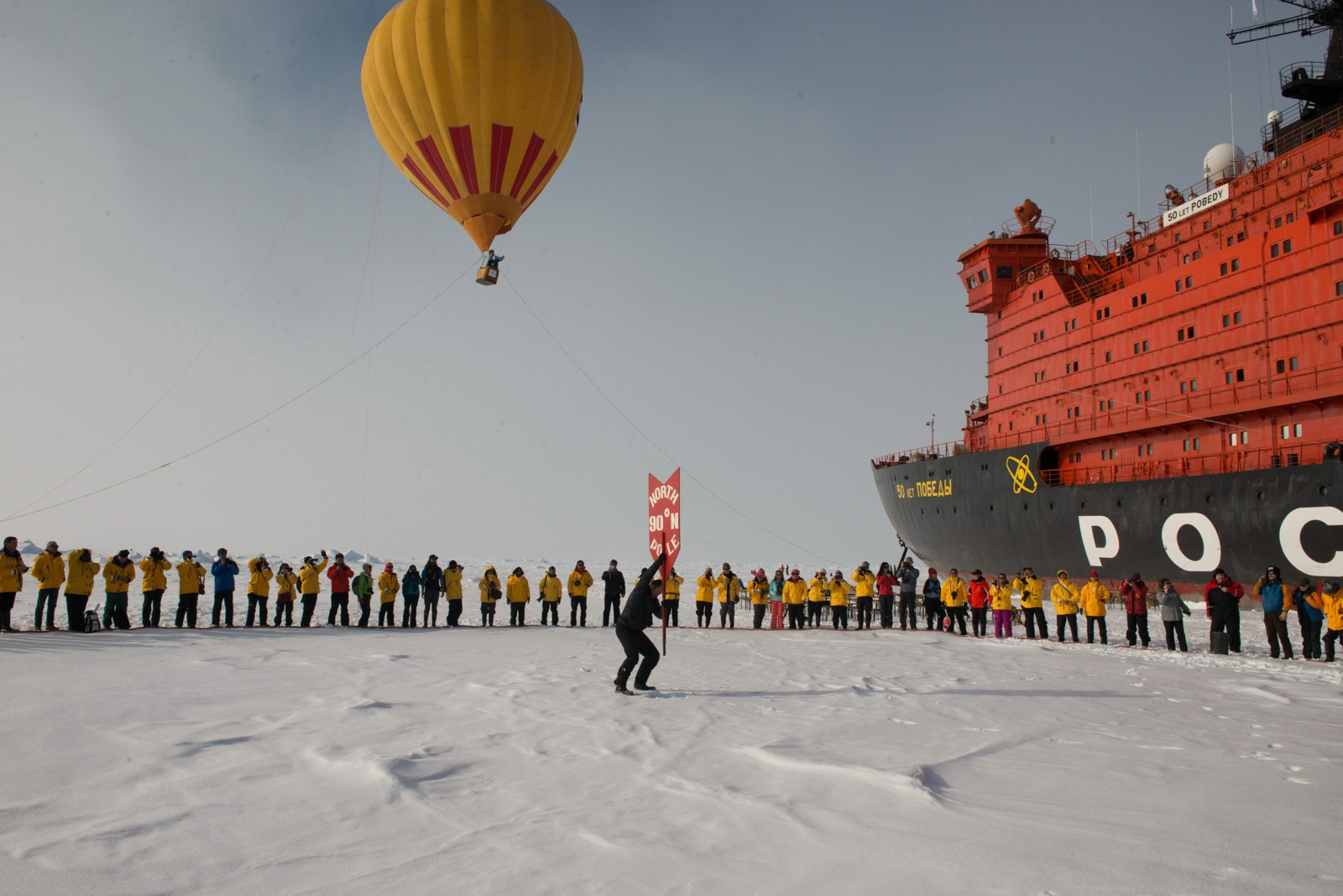 A hot air balloon flies high overhead as North Pole expedition passengers celebrate reaching their destination.