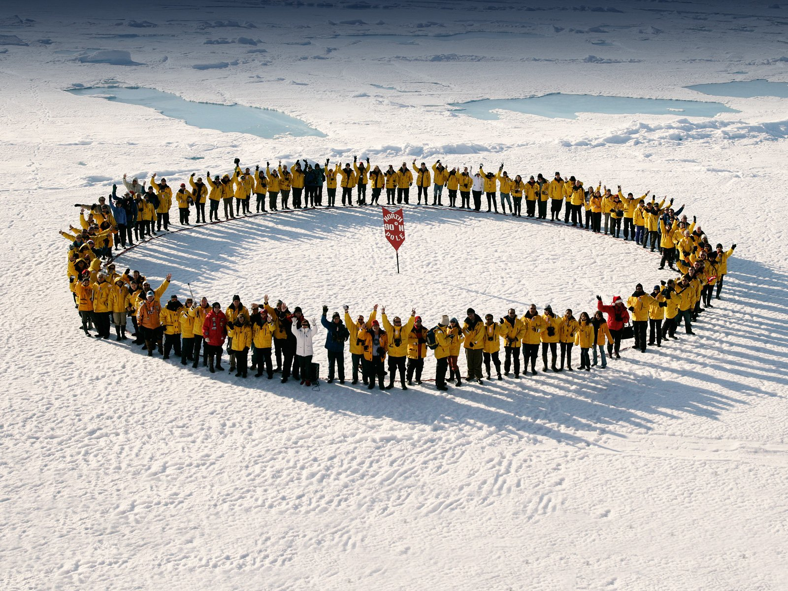 Passengers gather on the sea ice to celebrate the feat of reaching the North Pole by small expedition ship. Photo: John Weller