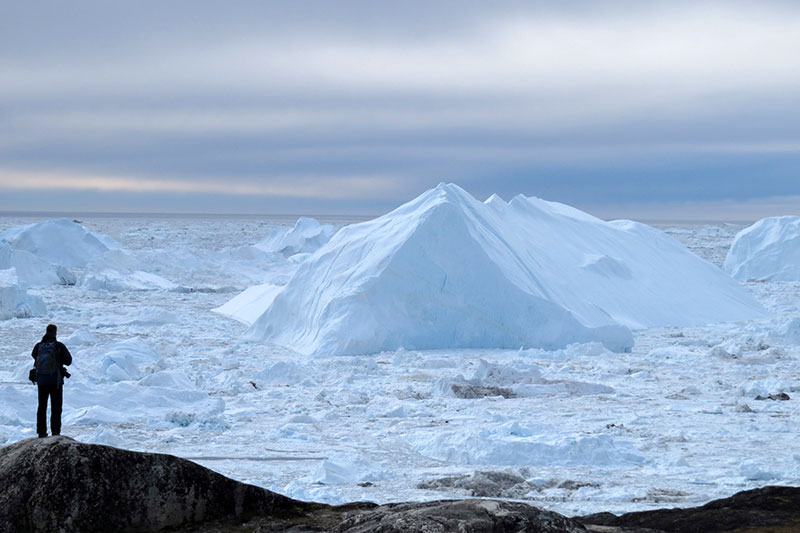 A Quark passenger enjoys the spectacular Arctic ice at Ilulissat, Greenland.