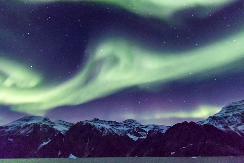 The Aurora Borealis or Northern Lights can be especially vibrant and colorful in Greenland. Photo credit: C King