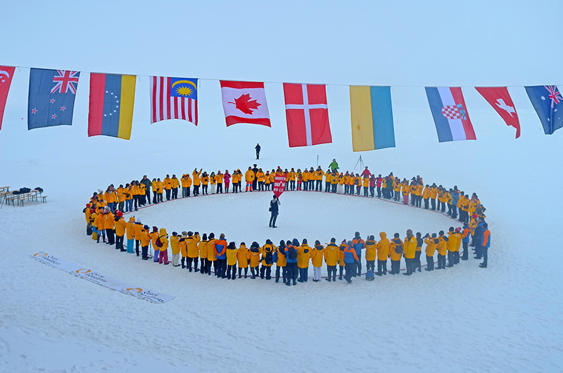 Quark passengers at the North Pole, framed by flags-Arctic