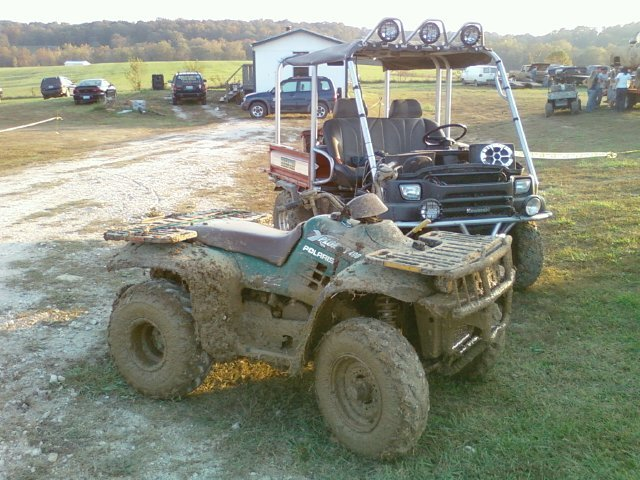 Showing off my muddy polaris next to my cousin's UTV