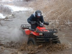 Tommy on his Polaris going through mud