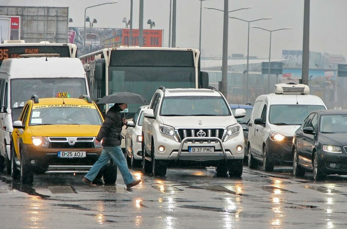 Cars and trucks stopped as a pedestrian crosses the street on a rainy day | Rubber products