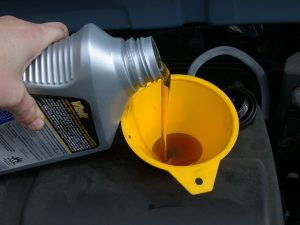 pouring oil into a filter for a car oil change