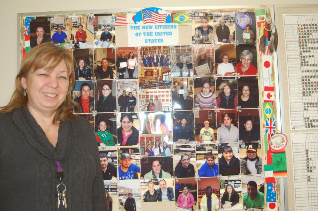 Victoria Dubrovina stands next to a collage of her students who are now US citizens.