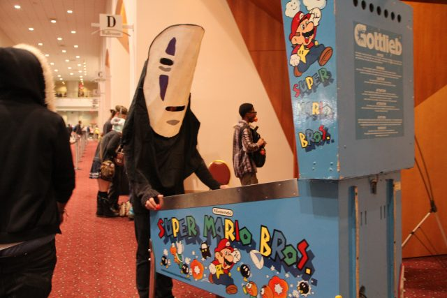 Cosplayer visits the gaming section on Sunday dressed as Noface from Spirited Away.