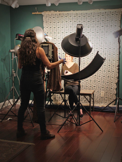 Margaret Muza prepares to take a tintype of our producer, Makenzie.