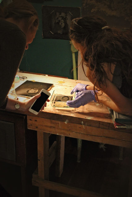 Margaret and Makenzie watch the final tintype photo slowly develop after the darkroom process.