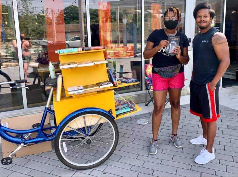 Main image. Cetonia Weston-Roy with a customer and her bookmobile that sells works by Black authors.