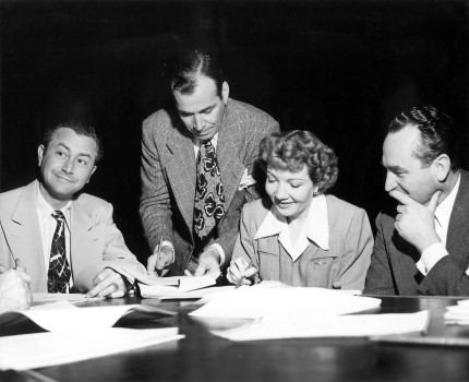 "Rehearsing the script for ""The Palm Beach Story"" are Robert Young, Harold Lloyd, and Claudette Colbert."