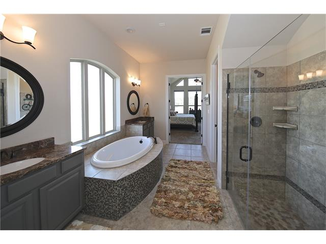 Master bathroom from view from the closet.  Walk-in shower and soaking tub with separate vanities.
