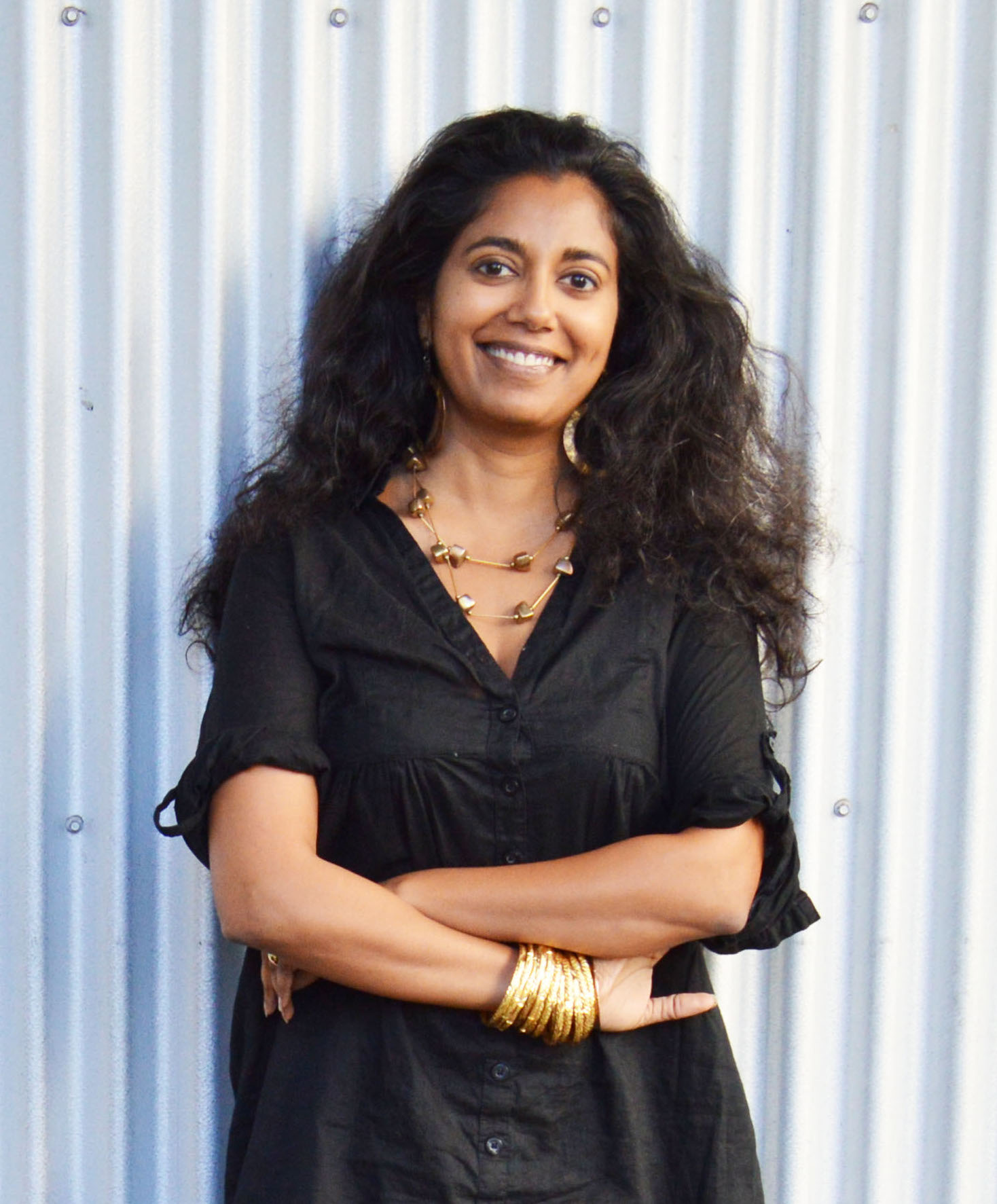 A picture of Mayanthi Fernando standing outside smiling against a white wall