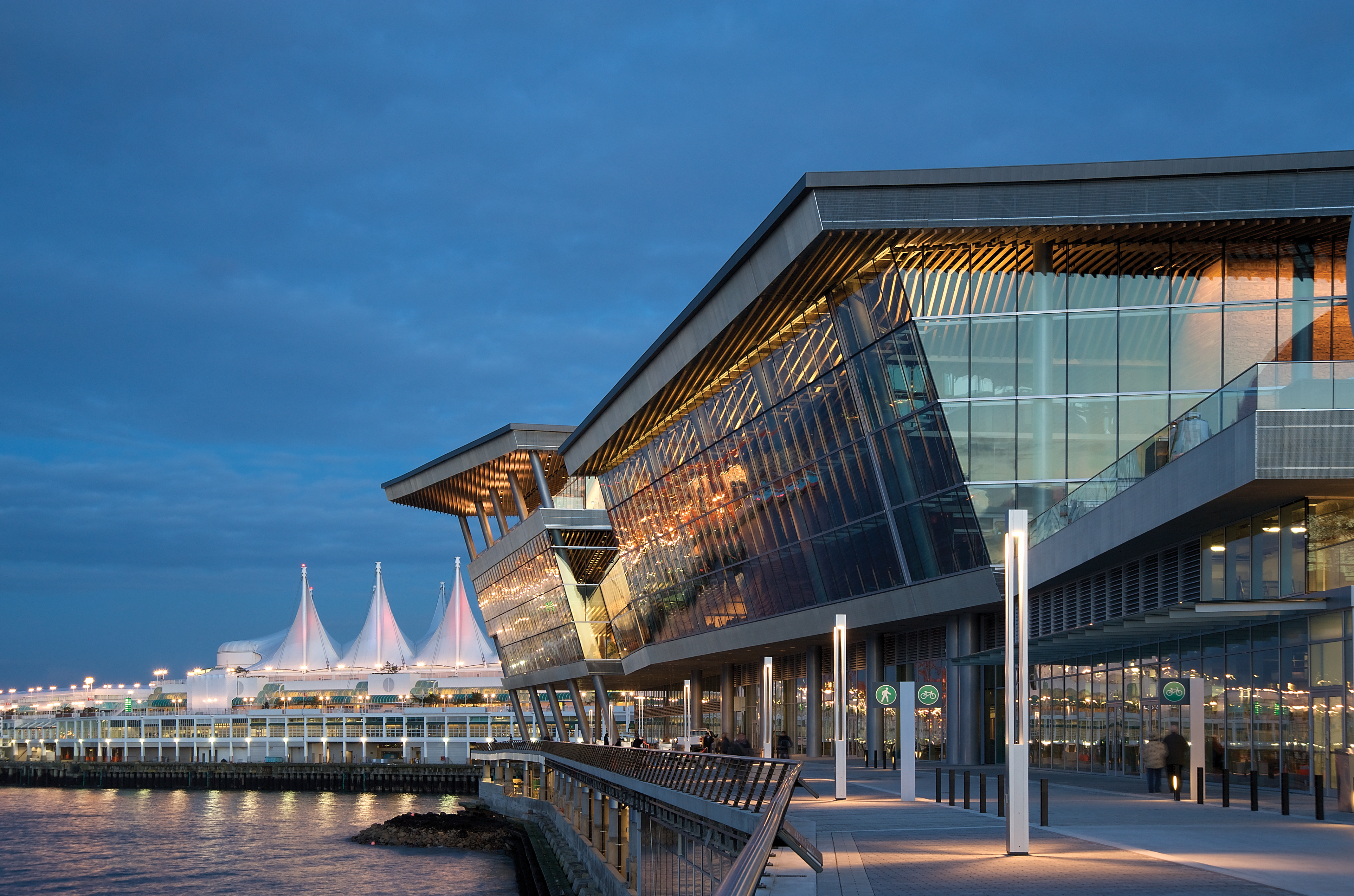 A picture of the Vancouver Convention Centre at dusk with lights on in the glass building sitting on the edge of the water.