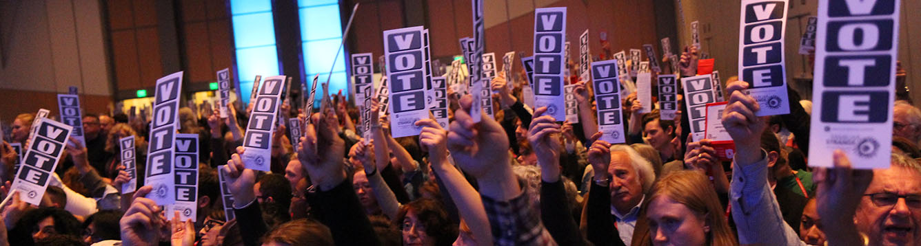 A room full of people hold up small signs that rea