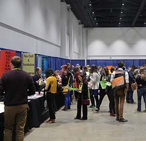 Image of people walking around an exhibit hall wit