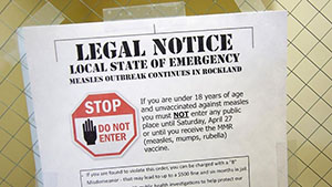 "A picture of a flyer taped against a wall. The flyer reads in all caps, ""Legal Notice. Local State of Emergency. Measles outbreaks continues in Rockland."" Underneath in smaller text, ""If you are under 18 years of age and unvaccinated against measles you must not enter any public place until Saturday, April 27 or until you receive the MMR (measles, mumps, rubella) vaccine."" Beside this text is an octagon stop sign with the text, ""Stop. Do not enter"" beside a hand. There is a small box of illegible text underneath."