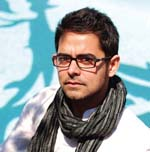 A portrait of Harjant Gill, a light-skinned man. He wears a scarf.