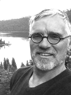 A black and white picture of Dr. Ken C Erickson, a light-skinned man, against a forest lake background.