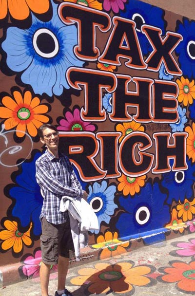 "A picture of Samuel Gerald Collins, a light-skinned man, standing against a large mural of flowers and the text ""Tax the rich.""]"