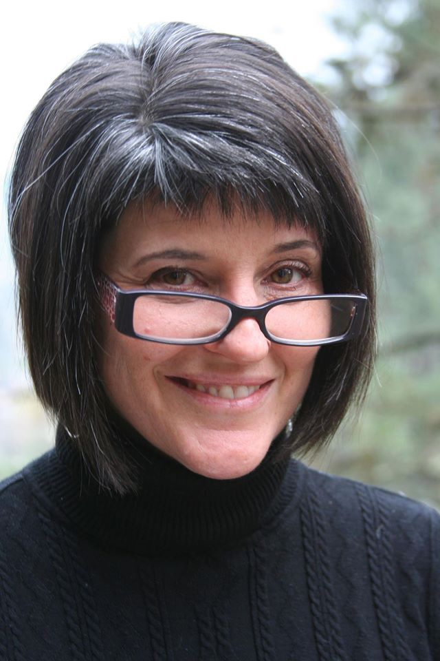 A portrait of Dr. Karen Kelsky, a light-skinned woman, smiling at the camera wearing a black turtleneck sweater.