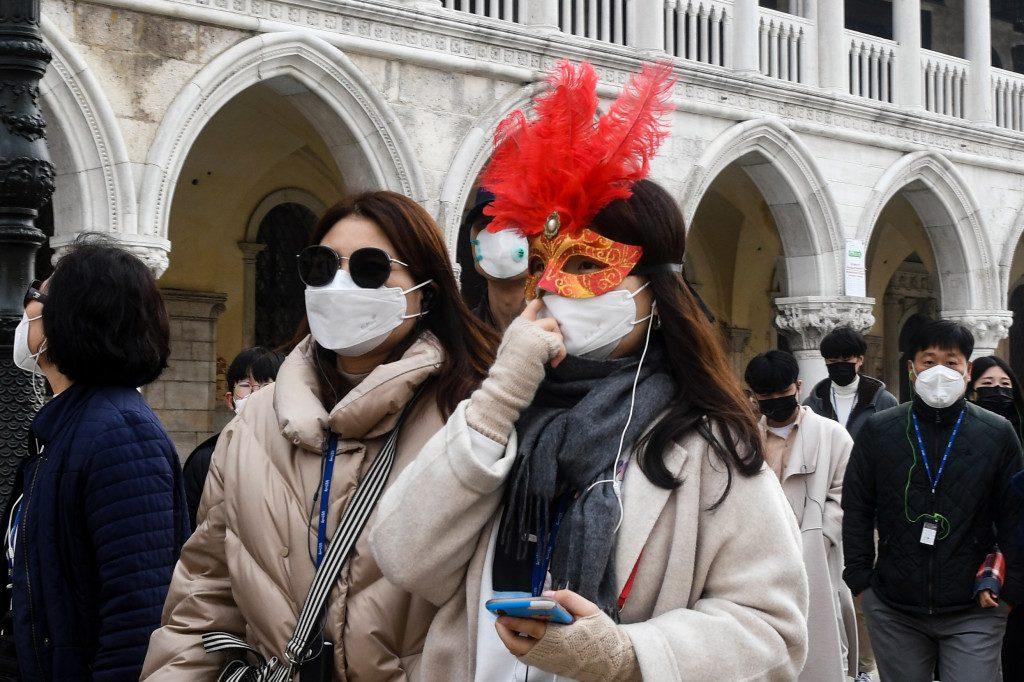 Tourists wearing protective facemasks and a Carnival mask visit the Piazza San Marco, in Venice, on Feb. 24, 2020. ANDREA PATTARO/AFP VIA GETTY IMAGES