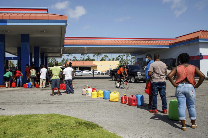 Residents wait in line to fill their containers with gasoline before the arrival of Hurricane Isaias in Freeport, Grand Bahama, Bahamas.AP