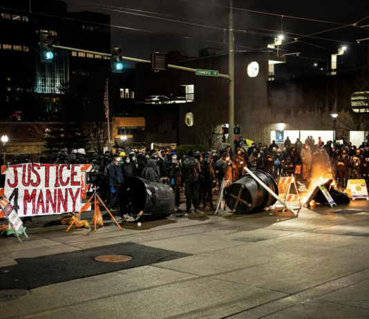 A barricade, with a banner referencing the 2020 death of Manuel Ellis in police custody, burns in an intersection in downtown Tacoma during an anti-police protest Getty Images