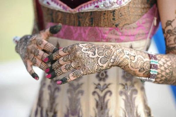 A complex henna design going up the arms of a bride