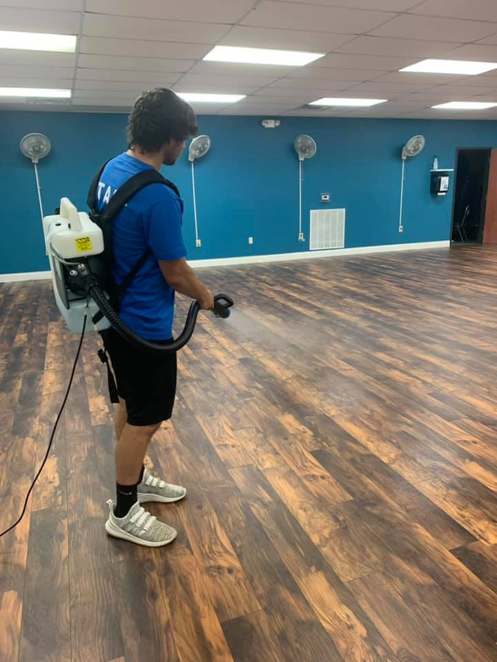 Barnwell YMCA staff using a disinfectant fogger to clean group exercise class gym.