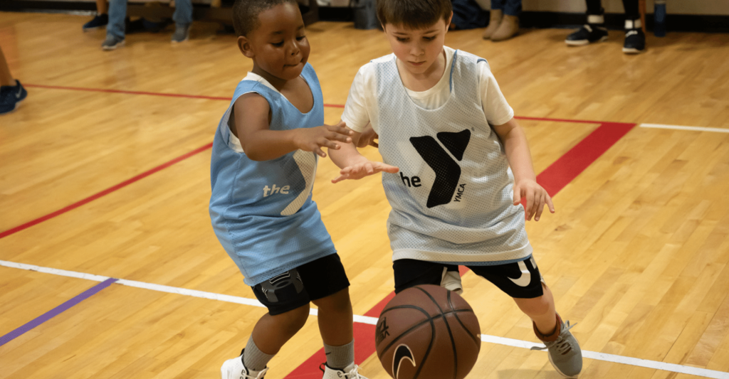 two young boys playing against eachother in a basketball game; they are both trying to get the basketball