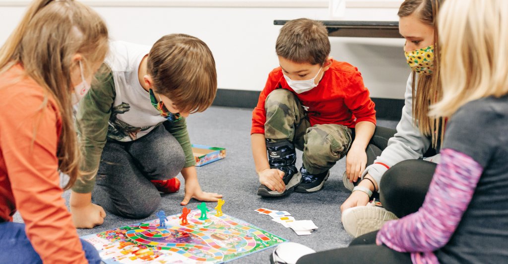 a group of young kids are gathered on the floor sitting around a board game with their teacher