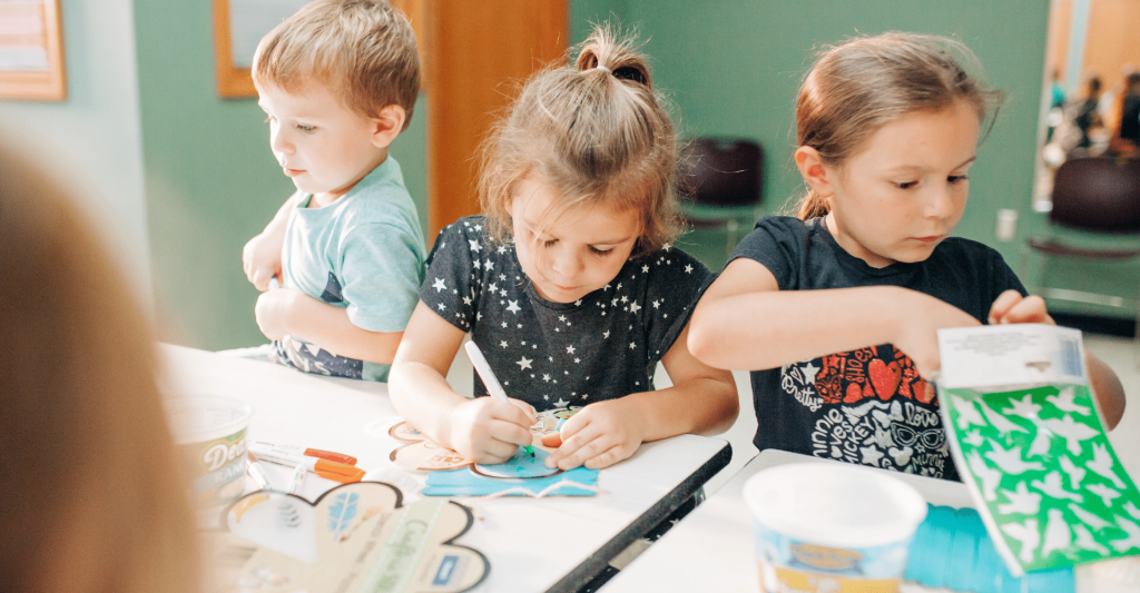 three young children sit together at a table while they do a craft together.