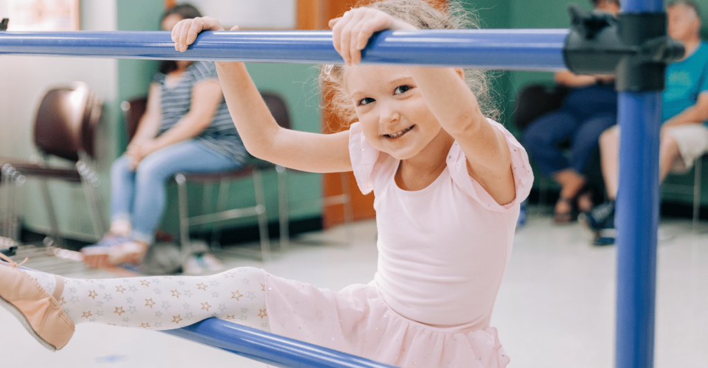 child wearing pink leotard in a dance class; she has her hands on a ballet bar