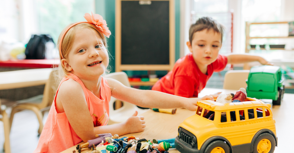 two young children are sitting at a table in a classroom playing with toy trucks and toys. They are smiling as they pretend to push the trucks on the table.