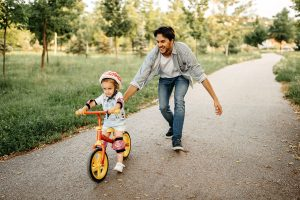 Father Helping Daughter Ride a Bike