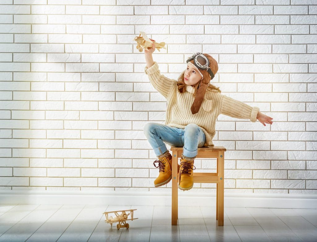 girl-playing-with-toy-airplane-P7BZC5C