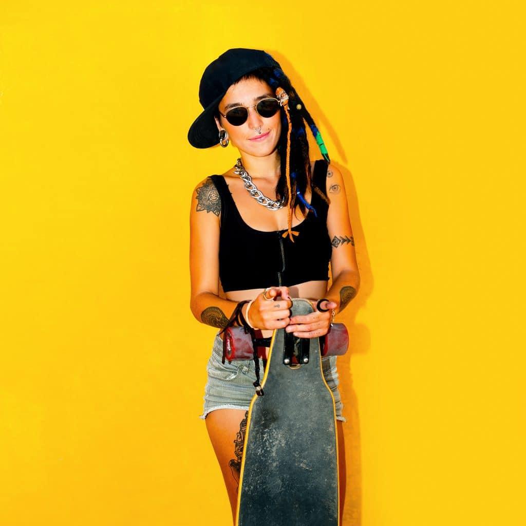 Fashion teenager girl with dreadlocks and tattoos. Skateboard  s