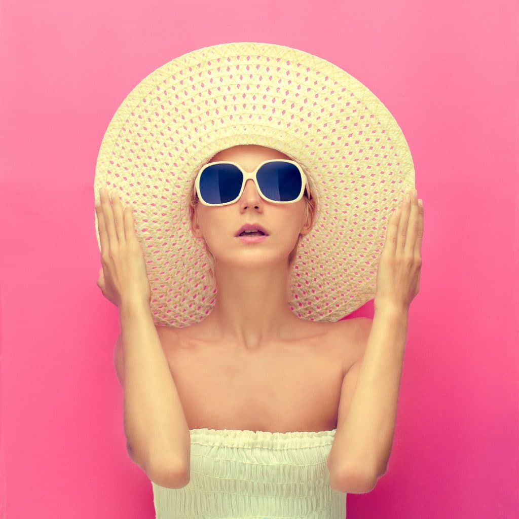 portrait-of-a-girl-in-a-hat-on-a-pink-background-P9TRMBK