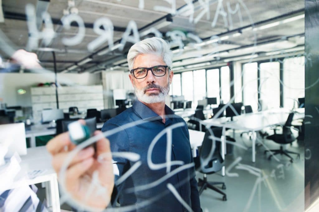 mature-businessman-with-gray-hair-in-the-office-PLVJZ7Y