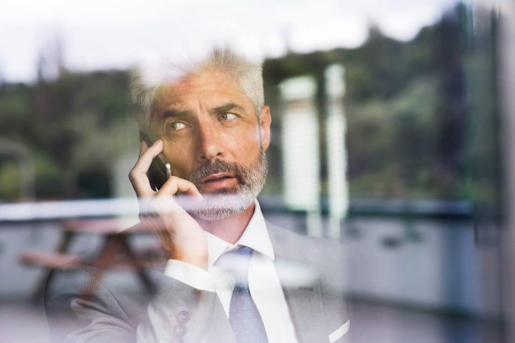 mature-businessman-with-smartphone-in-the-office-P8ZXQJ2